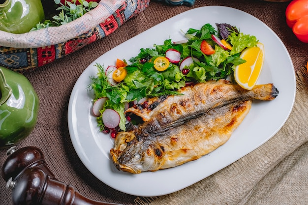 Top view of roasted fish served with fresh vegetables and lemon on a plate