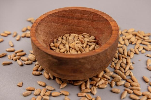 Vista dall'alto di semi di girasole sgusciati tostati su una ciotola di legno con semi sgusciati isolati