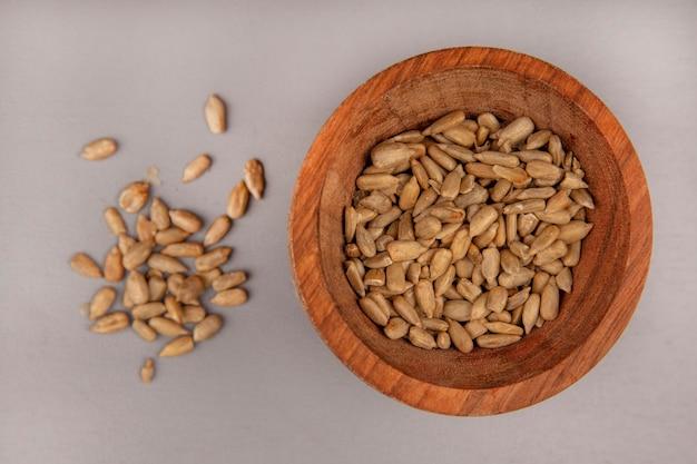 Vista dall'alto di semi di girasole sgusciati tostati su una ciotola di legno