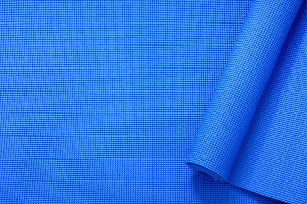 Top view roll of blue color yoga mat texture background, sport and exercise concept