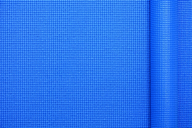 Top view of roll blue color yoga mat texture background