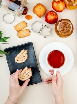 Top view of roll cake on a black tray served with a cup of tea and a glass jar with peach jam cookies fresh ripe nectarines and cookie cutters on white