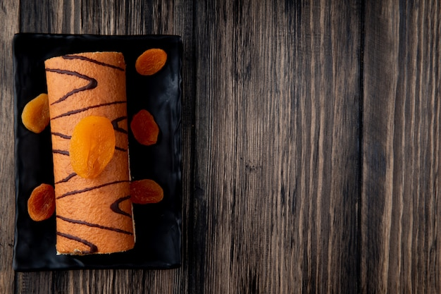 Top view of roll cake decorated with dried apricots on a black tray on rustic wood with copy space