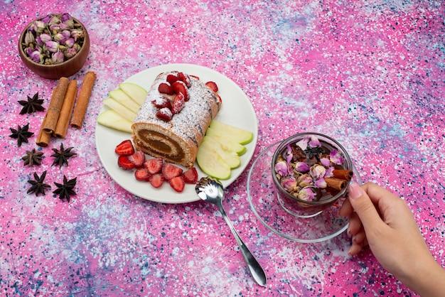 Ролл-торт, вид сверху, внутри тарелки с яблоками и клубникой вместе с корицей и чаем на цветном письменном торте, бисквитном сладком фрукте