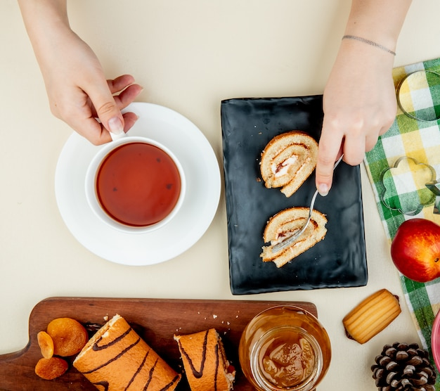 Top view of roll cake laying on a black tray and holding a cup of tea and a glass jar with peach jam cookies fresh ripe nectarines and cookie cutters on white