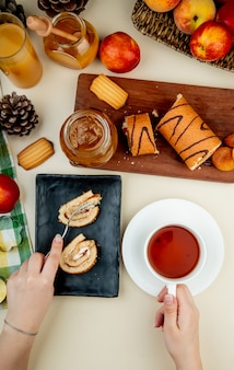 Top view of roll cake laying on a black tray and holding a cup of tea and a glass jar with peach jam cookies fresh ripe nectarines and a glass of juice on white