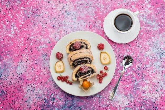 Вид сверху рулонных кусочков торта с разными фруктами внутри белой тарелки вместе с чашкой кофе на цветном фоне бисквитного торта сладкого цвета