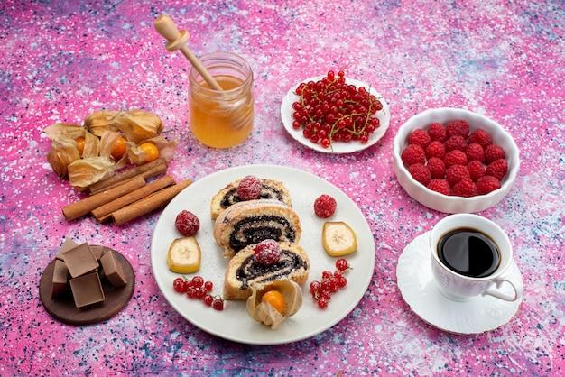 Fette di torta rotolo vista dall'alto con diversi frutti all'interno del piatto bianco insieme al miele sul colore dolce del biscotto della torta del pavimento luminoso