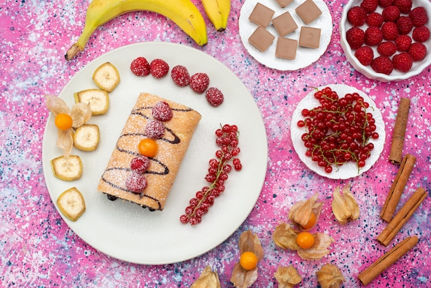 Top view roll cake slices with different fruits inside white plate on the colored background biscuit sweet color