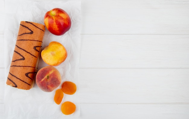 Top view of roll cake with fresh peaches and dried apricots on white with copy space