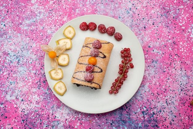 色付きの背景のケーキビスケット甘い色の白いプレート内の果物と平面図ロールケーキ