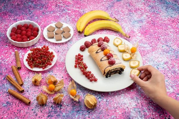 色付きのデスクケーキビスケット甘い色の白いプレート内のフルーツと平面図ロールケーキ