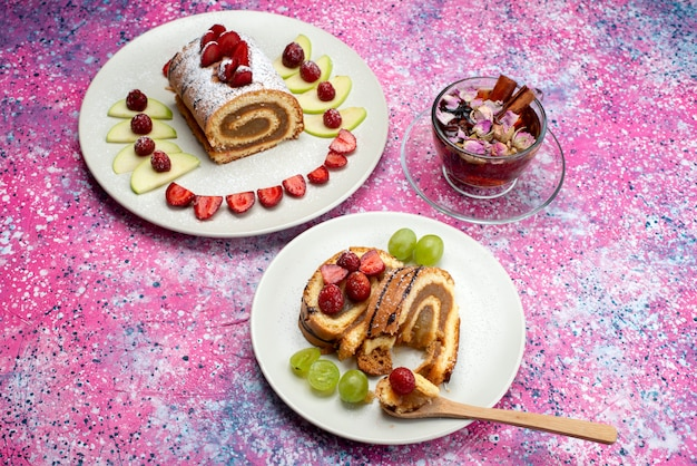 Top view roll cake with fruits inside white plate with tea on the colored background cake biscuit sweet color