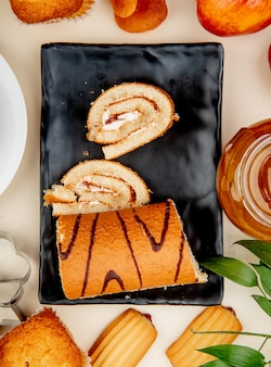 Top view of roll cake with peach jam on black tray on white