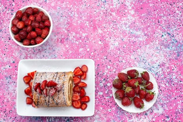 Ролл торт с красной клубникой внутри тарелок на цветном фоне торт бисквит сладкого цвета вид сверху