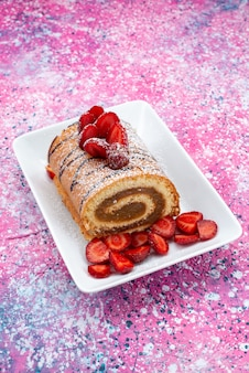 Top view roll cake with red strawberries inside white plate on the colored background cake biscuit sweet color