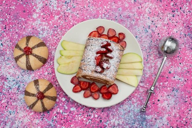 Вид сверху ролл торт с клубникой и яблоками внутри белой тарелки на цветном фоне бисквитный торт сладкого цвета