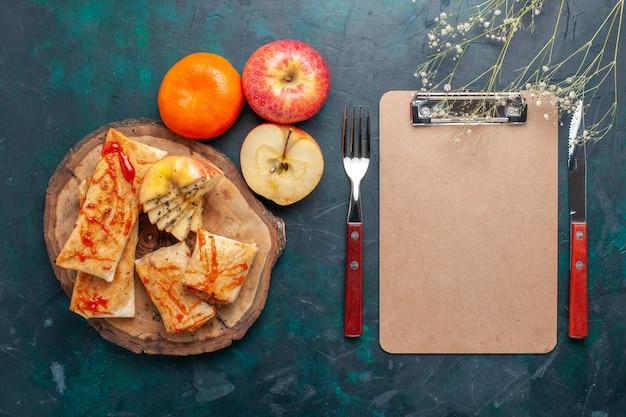 Vista dall'alto impasto arrotolato pita affettato con salsa e frutta sulla scrivania blu scuro