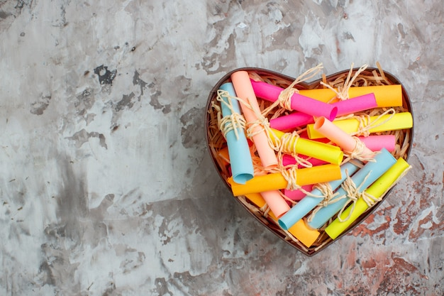 Top view rolled up colored sticky notes in heart shaped box on table with