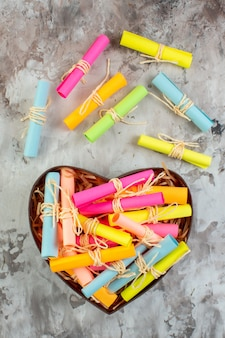 Top view rolled up colored sticky notes in heart shaped box on table