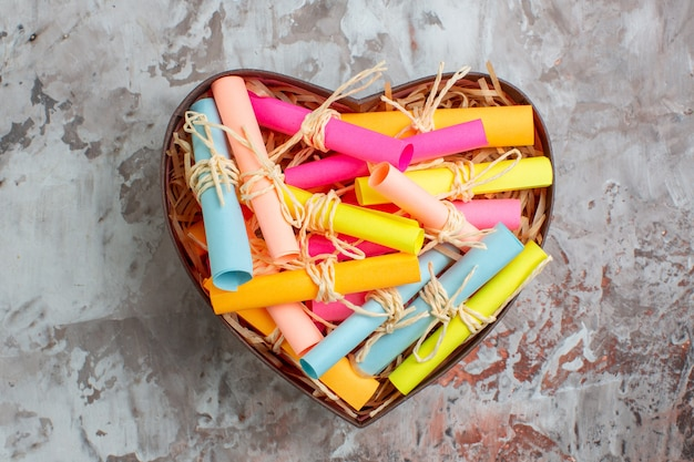 Top view rolled up colored sticky notes tied with rope in heart shaped box on table