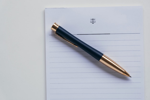 Top view of a rollerball pen placed on a piece of white striped paper