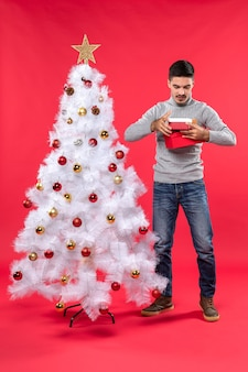 Top view of romantic adult in a gray blouse standing near the decorated white christmas tree and holding his gifts on red