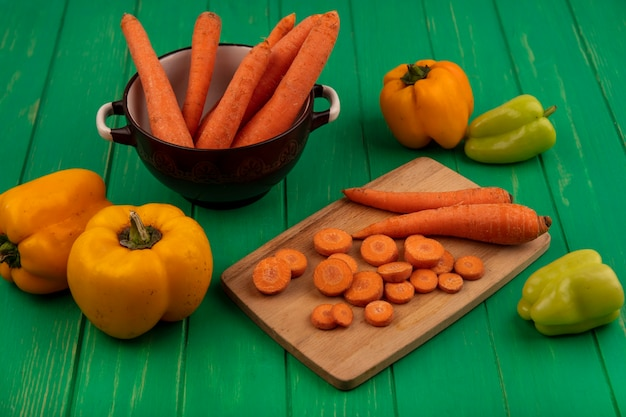 Top view of root vegetable carrots on a bowl with chopped slices on a wooden kitchen board with bell peppers isolated on a green wooden wall