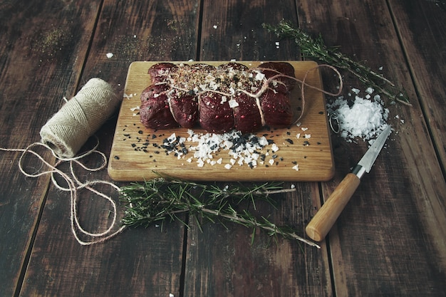 Top view rope tied salted peppered piece of meat ready to smoke on wooden table between herbs
