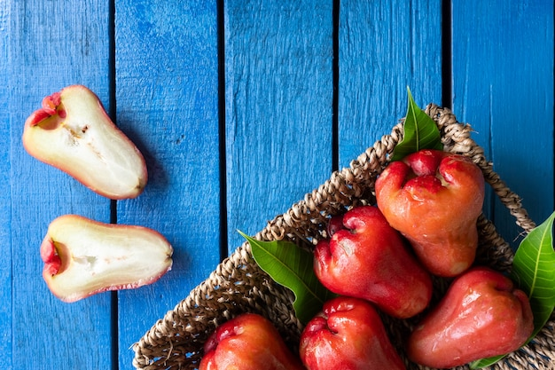 Top view of rose apples in basket on blue wooden table