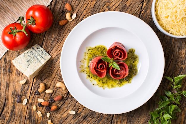 木製のテーブルにトマト、チーズ、バジル、ペストソースの上面図バラ形パスタ