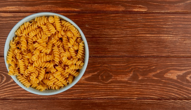Top view of rotini pasta in bowl on wooden surface with copy space