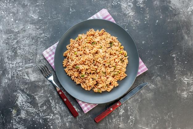 Вид сверху ротини макароны на круглой тарелке на розово-белых клетчатых салфетках, нож и вилка на сером столе