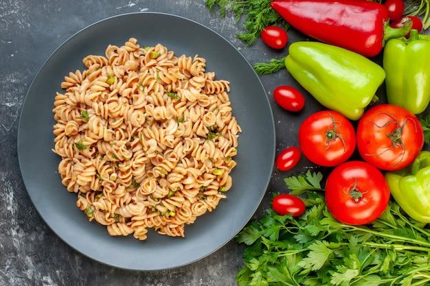 Pasta rotini vista dall'alto sul piatto rotondo peperoni pomodori prezzemolo aneto pomodorini sul tavolo grigio