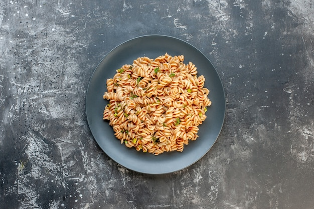 Top view rotini pasta on round plate on dark surface with copy place