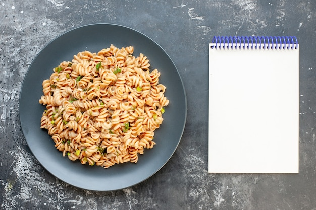 Top view rotini pasta on round plate notepad on dark surface