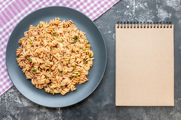 Top view rotini pasta on round plate on pink white checkered tablecloth notebook on dark surface