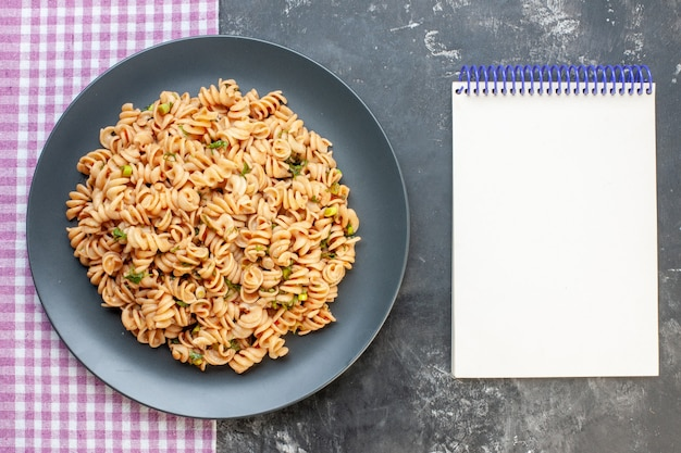 Top view rotini pasta on round plate on pink white checkered tablecloth notepad on dark surface food photo
