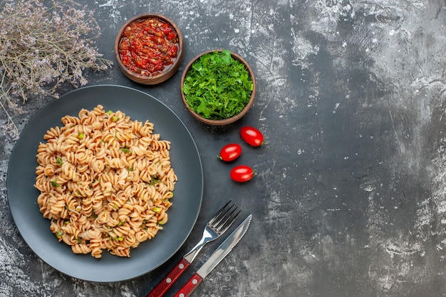Top view rotini pasta on round plate tomato sauce chopped parsley in small bowls cherry tomatotes fork and knife on dark table free space