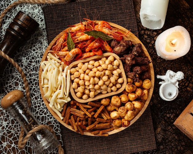 Top view of round beer snacks platter with shrimp chickpeas string cheese