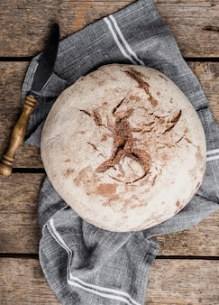 Top view round bread with knife on cloth