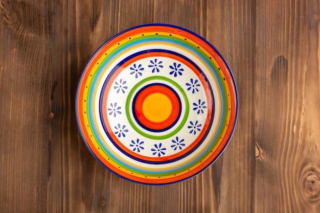 Вид сверху круглое красочное пластинчатое стекло на коричневом столе