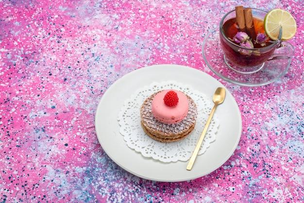 Вид сверху круглое печенье с французскими макаронами и чаем на цветном фоне сахарного сладкого торта