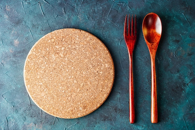 Top view of round cutting board between fork and spoon on rustic table background for menu with copy...