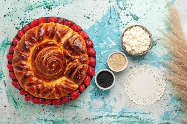 상위 뷰 라운드 맛있는 파이 구운 파란색 표면에 딸기와 달콤한 케이크