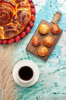 Vista dall'alto rotonda deliziosa torta con fragole rosse fresche sulla superficie blu