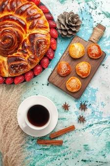 新鮮な赤いイチゴのケーキと水色の表面にお茶のカップとおいしいパイの周りの上面図