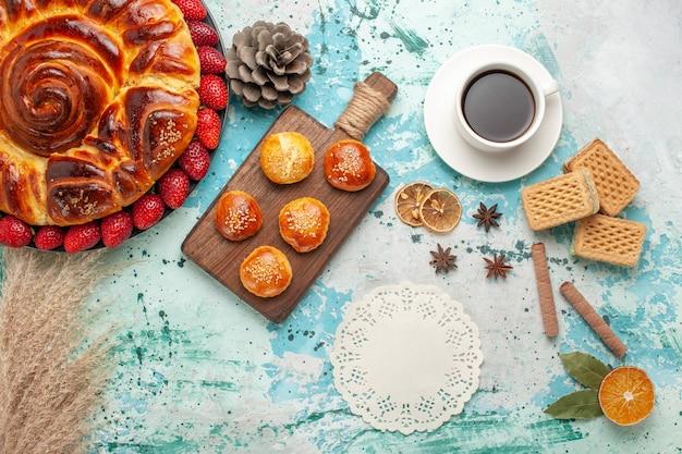 新鮮な赤いイチゴのケーキと青い表面にお茶のカップとおいしいパイの周りの上面図