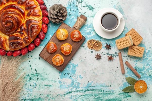 Vista dall'alto rotonda deliziosa torta con torte di fragole rosse fresche e tazza di tè sulla superficie azzurra
