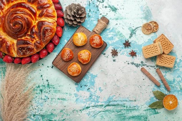 Vista dall'alto rotonda deliziosa torta con fragole rosse fresche torte e waffle su superficie azzurra